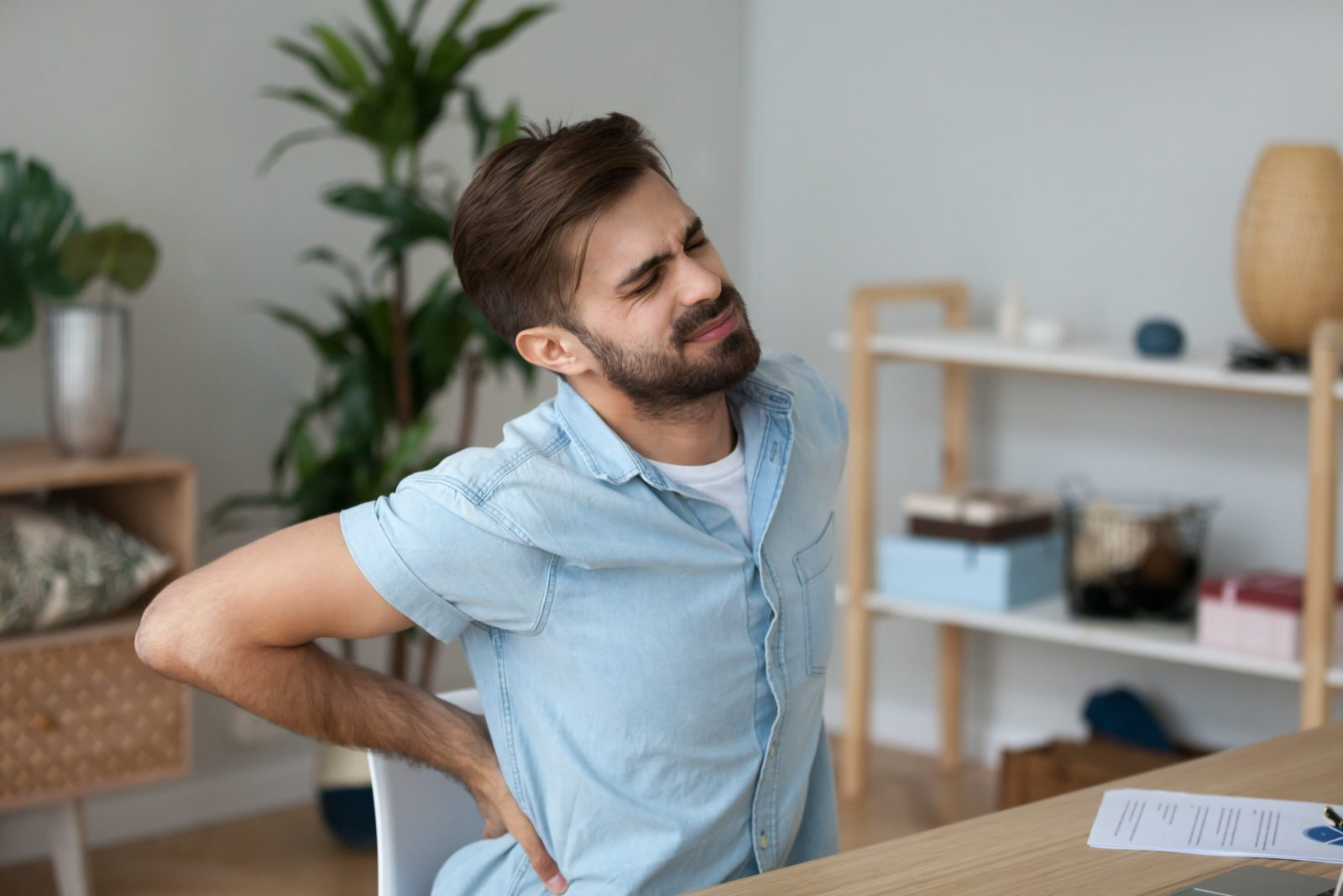 man sitting at desk wincing and holding his back in pain