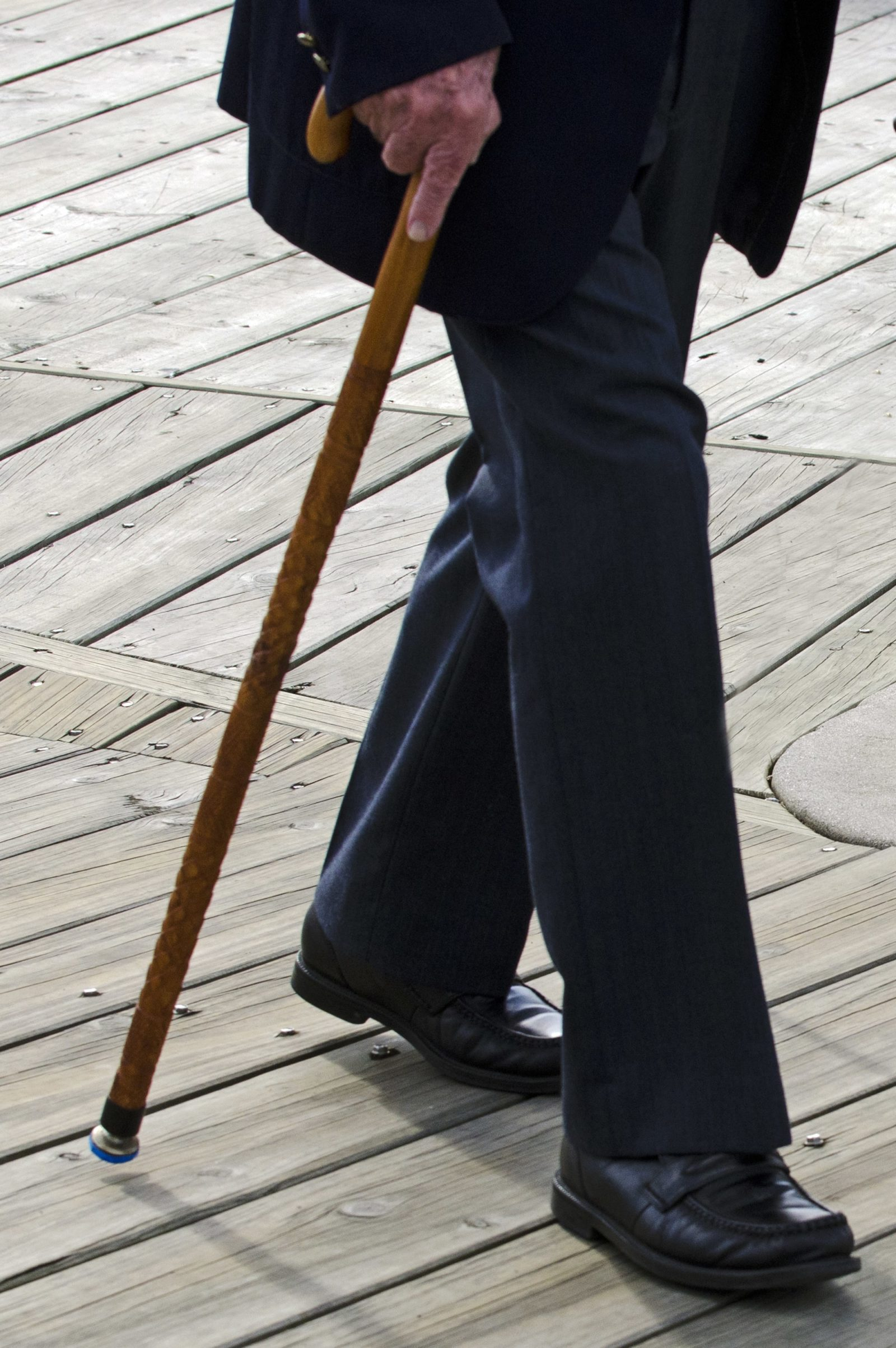 closeup of older man walking with a cane
