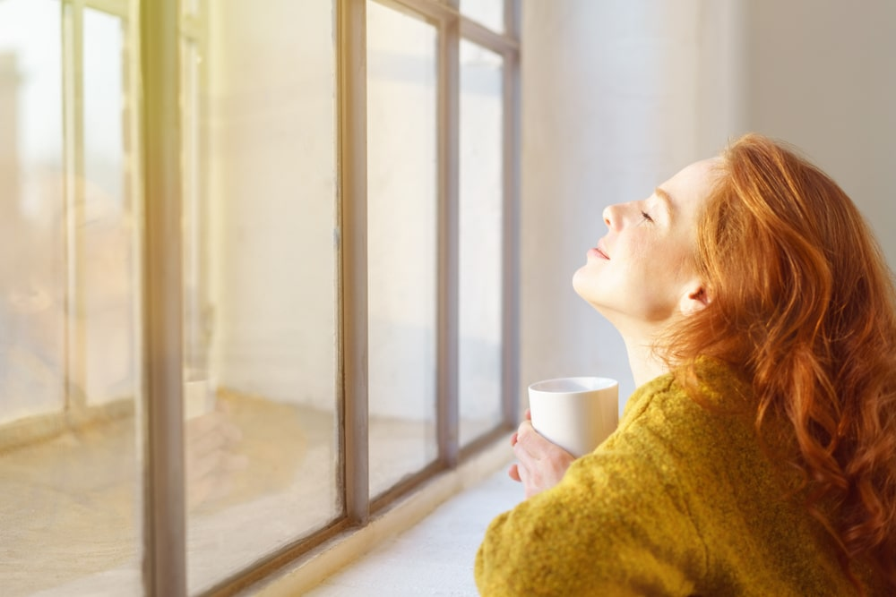 woman looking out a sunny window