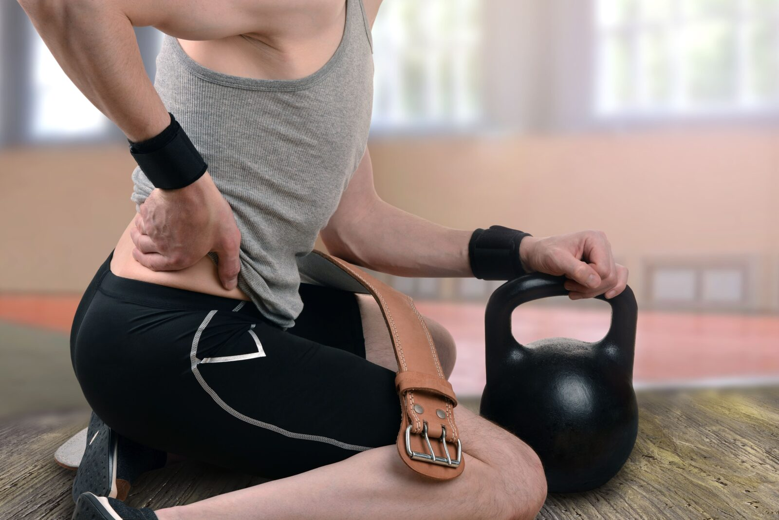 kneeling weight lifter clutching their lower back